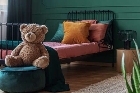 Teddy bear on velvet emerald green pouf in fashionable teenager bedroom interior with single bed