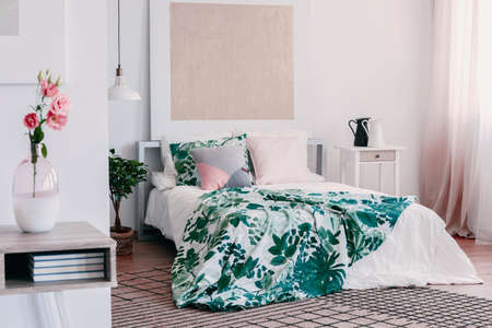 Pink roses in glass vase on wooden table in elegant bedroom interior with comfortable bed, plant in pot and carpet on the floor