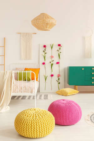 Yellow and pink pouf in the middle of boho female bedroom with green cabinet, flower board, single bed and macrame on the wall Stock Photo