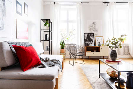 Red pillow and blanket on couch in bright loft interior with flowers on table and armchair. Real photo