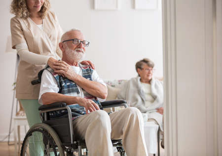 Senior man in a wheelchair assisted by a young nurse Stock Photo