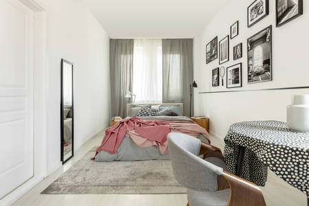 Table with doted tablecloth in bright bedroom interior with white empty wall, mirror and king size bed with grey bedding and pastel pink blanket