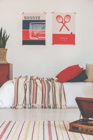 Oldschool graphics on a wall in a bedroom interior with a bed and striped rug Stock Photo