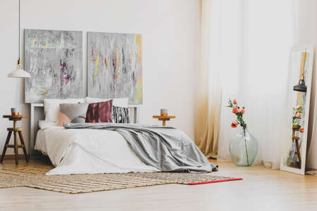 Natural rug on wooden floor of stylish bedroom interior with king size bed, wooden nightstands and grey fancy paintings on white wall Stock Photo