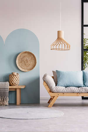 Wicker chandelier above wooden Scandinavian sofa with futon in bright living room interior Stock Photo
