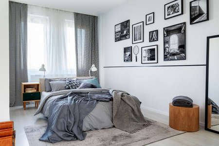 Checkered curtains on the window of contemporary bedroom interior with wooden nightstand and king size bed with grey bedding Stock Photo