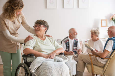 Disabled grandmother in a wheelchair supported by a nurse in a common room in a care home Stock Photo