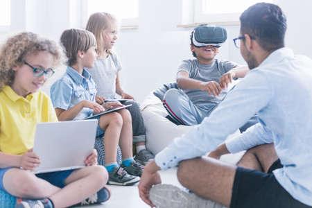 Niño fascinado usa gafas de realidad virtual durante una lección de tecnología para niños en una escuela innovadora