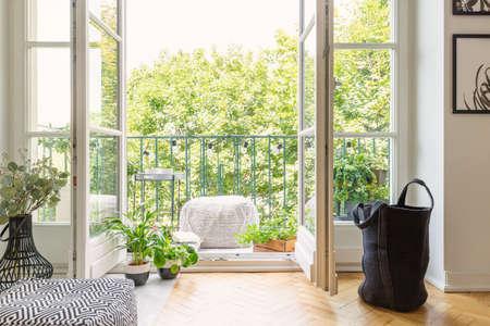 Foto real de puerta abierta al balcón con muchas plantas frescas, luces, puf de material y vista a la jungla urbana. Foto de archivo