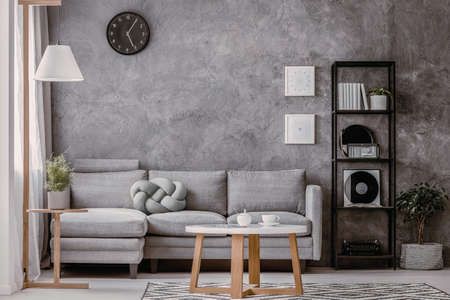 Copy space and black clock on grey concrete wall in chic living room with industrial black metal bookshelf next to corner sofa with pastel grey knot pillow
