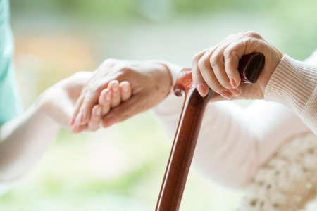 Close-up van senior grootmoeder met wandelstok in de ene hand en de hand van kleindochter in de andere