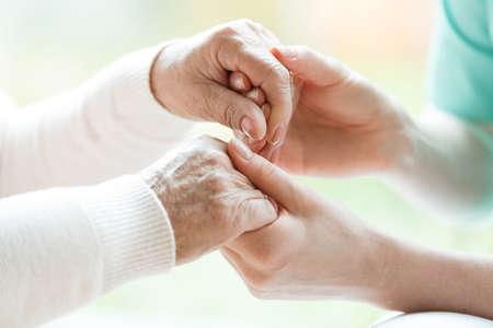 Close-up van handen van jonge kleindochter die de handen van haar grootmoeder vasthoudt