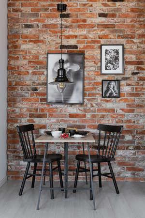 Galerij van zwart-wit posters op bakstenen muur van kleine eetkamer interieur met tafel en zwarte stoel