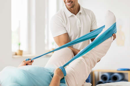 Physiotherapist supporting his patient with leg rehabilitation