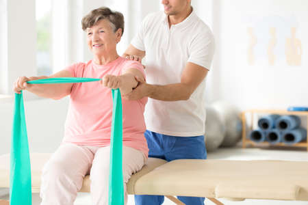 Happy senior during rehabilitation with an elastic band assisted by a physiotherapist 版權商用圖片