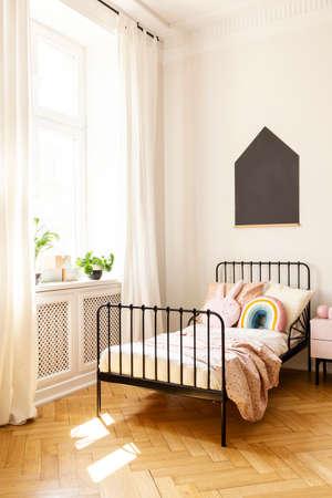 Piante sul davanzale della finestra all'interno della camera da letto del bambino con poster nero sopra il letto con cuscini. Foto reale