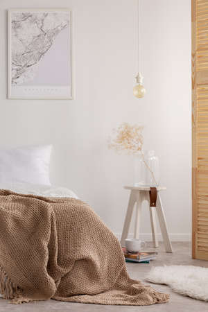 Vertical view of map on the wall of stylish bedroom with bedding made from natural materials and wooden bedside table, real photo
