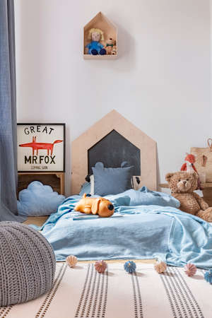 Real photo of a boy room interior with toys, bed and rug