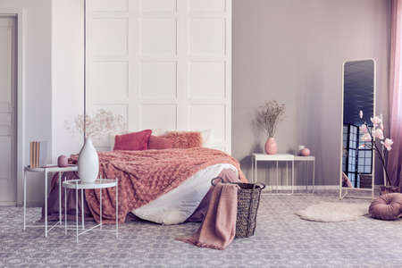 Bright bedroom interior with large comfortable bed with dirty orange pillows and cozy blanket Stockfoto