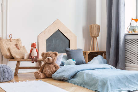 Teddy bear next to a bed covered with blue sheets in a natural kid room interior. Real photo