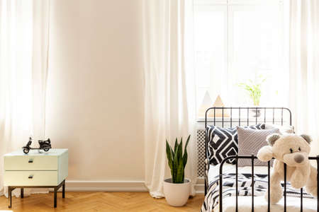 Teddy bear on child's bed in white bedroom interior with plant and copy space on the wall. Real photo Archivio Fotografico