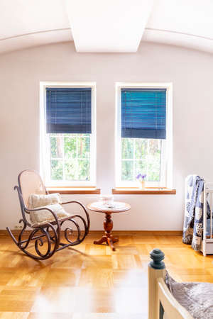 Wooden rocking chair next to table in living room interior with blue blinds at windows. Real photo Imagens