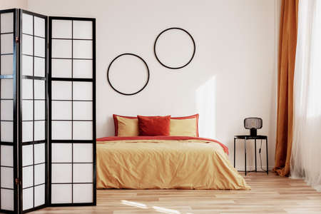 Round black frames on white wall of elegant bedroom interior with king size bed with yellow and ginger bedding