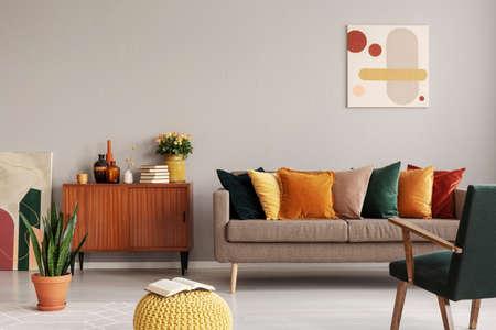 Pittura astratta sulla parete grigia dell'interno del soggiorno retrò con divano beige con cuscini, poltrona vintage verde scuro e pouf giallo con libro