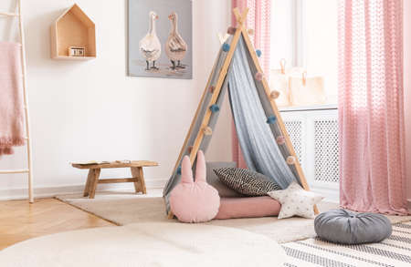 Real photo of a pink playroom for children with a tent, painting and wooden bench