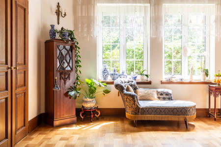 Wooden cabinet next to settee in bright elegant living room interior with door and windows. Real photo Imagens