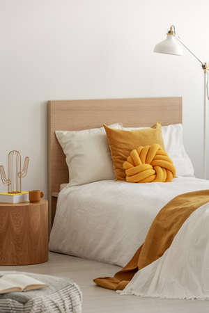 Yellow pillows and cozy blanket on single bed in elegant hotel room, copy space on empty white wall