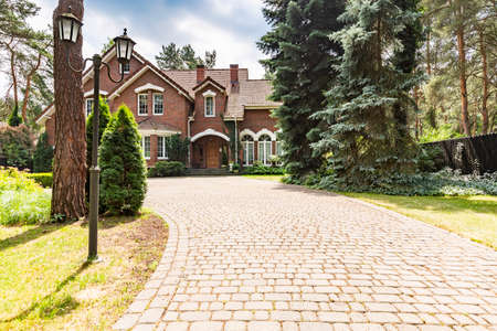 Driveway and trees on real estate with red brick house in english style with windows