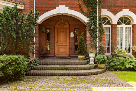 Plants, bushes and trees in front of wooden door of red brick mansion with windows Stok Fotoğraf