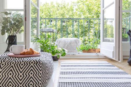 Pouf avec assiette rose avec tasse à café et croissant au premier plan flou en vraie photo de pièce avec plantes fraîches, tapis au sol et porte ouverte sur balcon