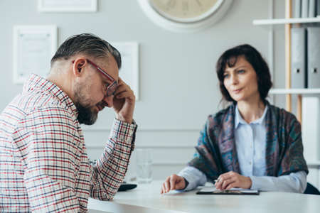 Young psychotherapist helping adult man with his problems