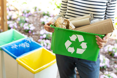 Cropped view of eco friendly woman holding green recycling box with paper waste Banco de Imagens