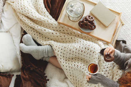 High angle on woman drinking hot tea while sitting on bed with blanket and tray