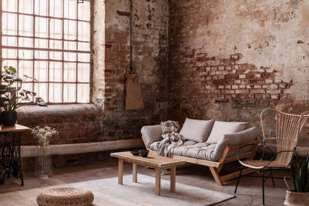 Pouf and wooden table on rug in bright living room interior in wabi sabi style with settee and armchair. Real photo