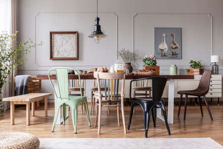 Colorful chairs at wooden table in grey rustic dining room interior with posters, flowers and table full of food, real photo Foto de archivo - 119191976