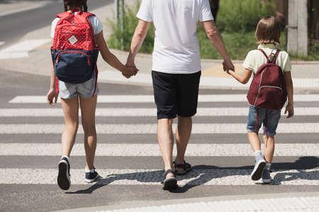 Responsible parent holding hands of children while walking through crosswalk
