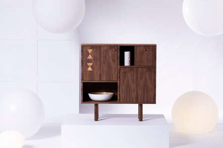 Real photo of a walnut wood sideboard standing against white wall in bright studio interior during product photo-shoot