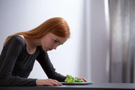 Junges Mädchen, das den Salat auf einem Tisch betrachtet Standard-Bild