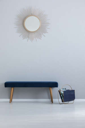 Navy blue bench placed in real photo of light grey entrance hall interior with basket with magazines and round decorative mirror hanging on wall