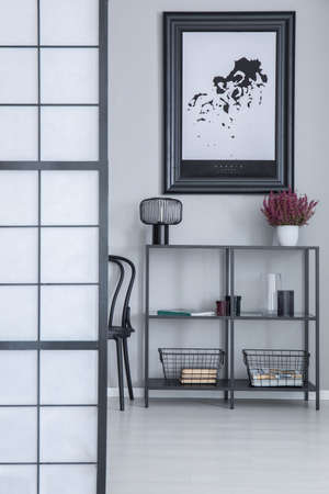 Industrial rack with lamp, fresh heather, metal baskets and decor standing in room interior with simple poster on light grey wall in real photo