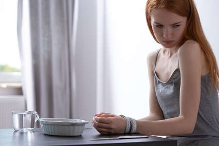 Skinny girl sitting at the table in front of a plate with hands tied with measuring tape 写真素材 - 119583672
