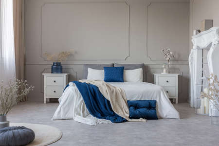 White fireplace portal, two nightstand with drawers and king size bed with petrol blue and white bedding