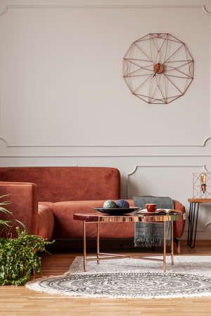 Interno alla moda del salone con il sofà d'angolo marrone con i cuscini e la coperta nell'interno alla moda del salone Archivio Fotografico