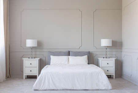 White bedding on king size bed, copy space on empty grey wall