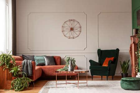 Sillón de terciopelo verde esmeralda con almohada naranja junto al sofá esquinero y la mesa de café