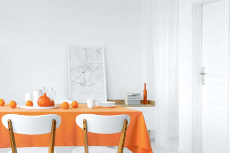 Table with oranges, pumpkin, dinnerware and juice placed in white dining room interior with cupboard with books and map poster in the real photo